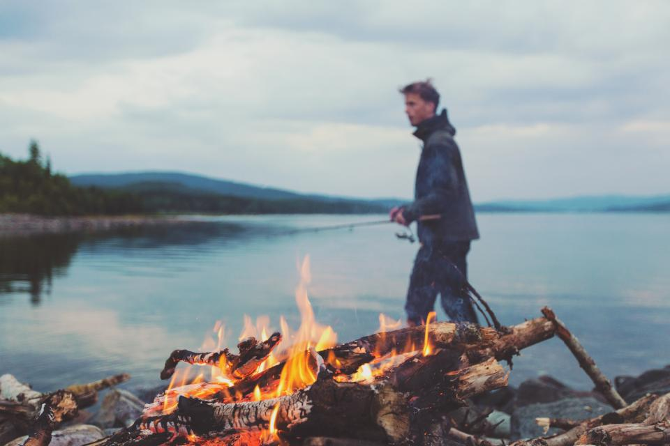 bonfire fire flames camping lumber logs young guy man fishing rod lake water camping nature people