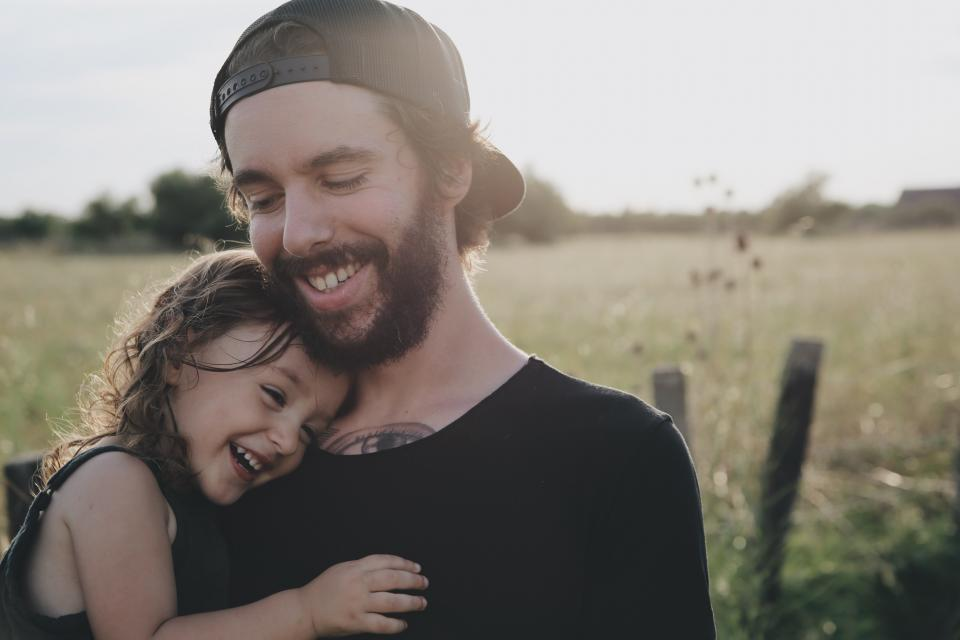 people father daughter smile happy hug carry love field trees beard cap child girl