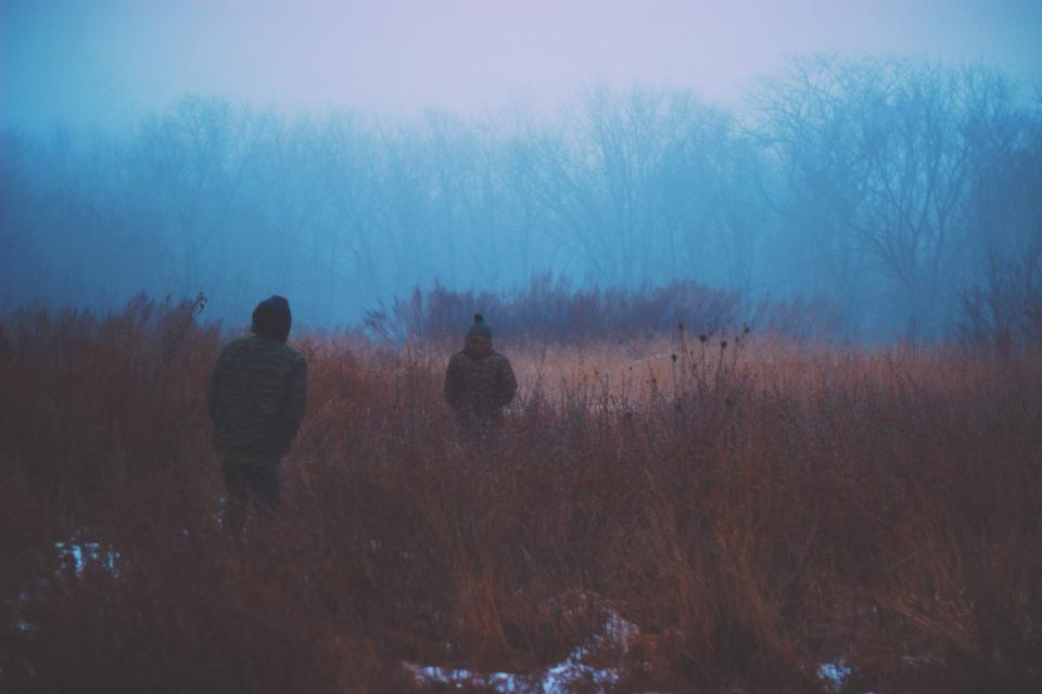 dark fog winter cold snow coats jackets people woods trees outdoors haze toque bushes