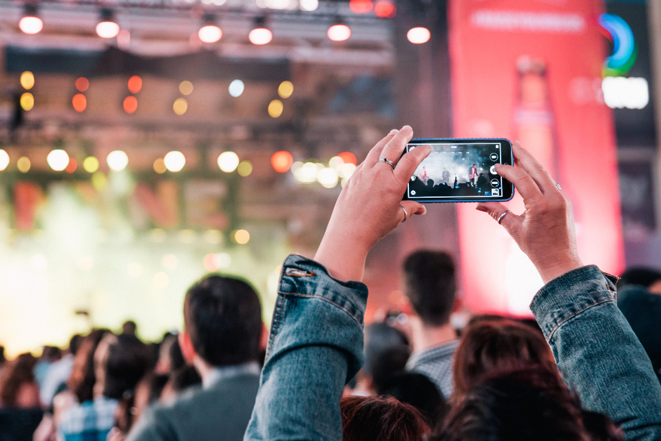 concert festival smartphone mobile phone event live venue band music audio hands musicians performance show stage taking photo audience crowd lights party people phone