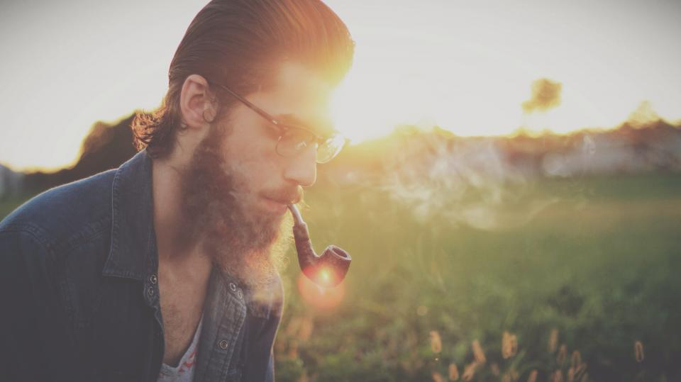 guy man beard hair glasses pipe smoke smoking field sunset denim people