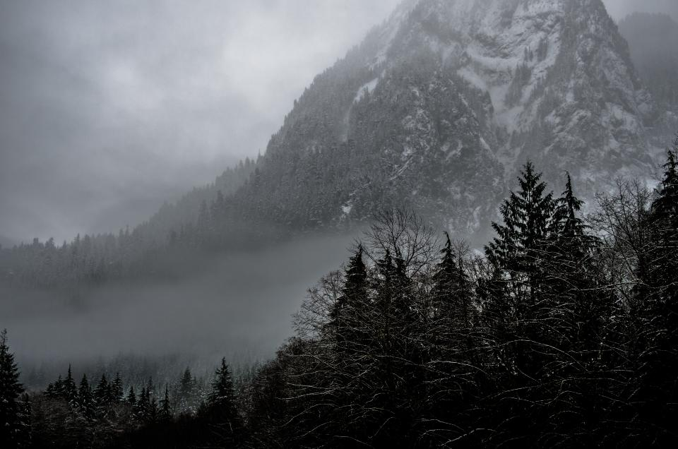 nature landscape mountains summit peaks forests trees fog clouds snow ominous