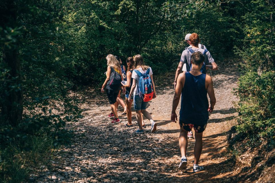 people men women backpack walking hiking adventure travel outdoor field trip trees plant nature path grass sunny summer