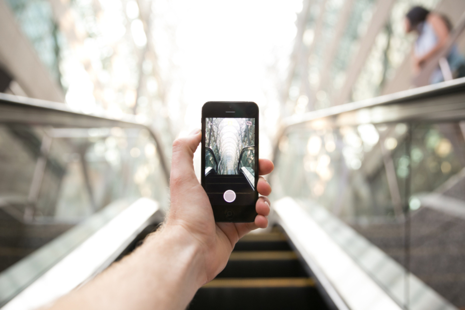 holding smartphone escalator stairs mobile wireless camera city urban digital technology modern hand taking picture phone