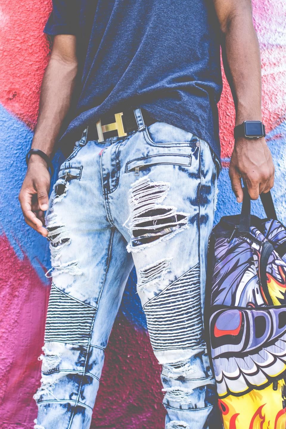 guy man fashion ripped jeans colorful wall graffiti art belt hermes watch bag african american clothing