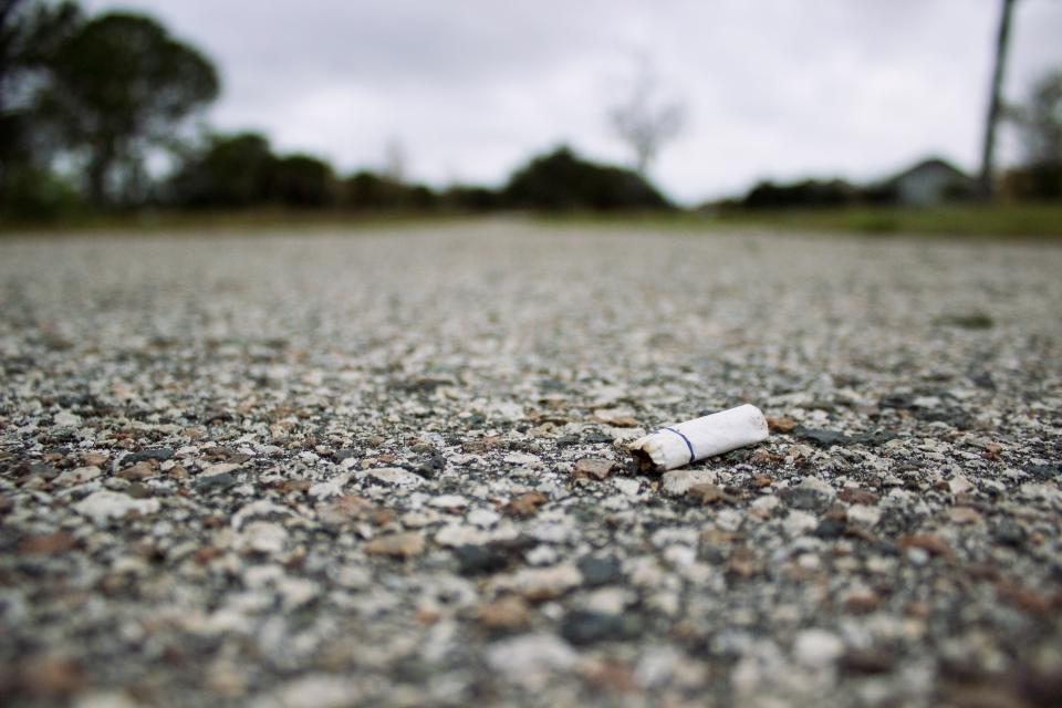 cigarette bud smoking pavement ground