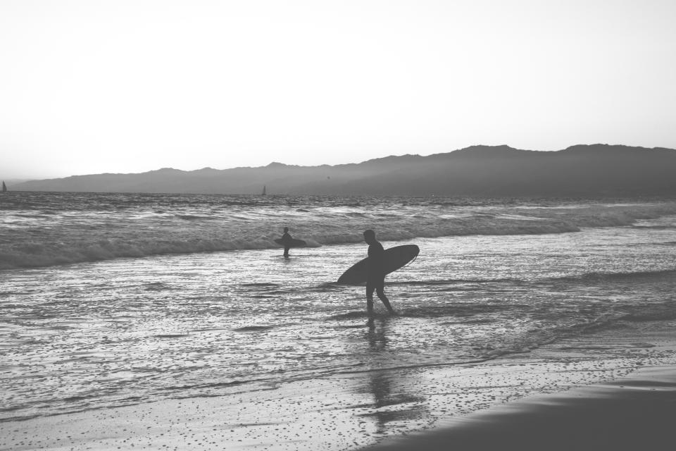surfing surfer surfboard beach sand water waves ocean sea black and white