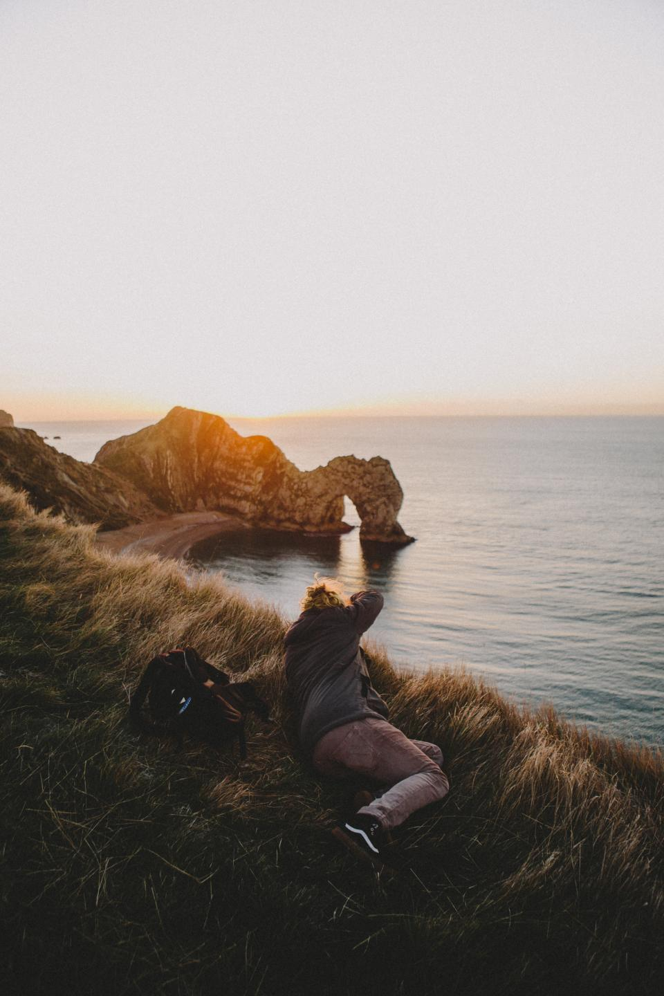 grass blur coast sea water sunrise cliff rocks view people man guy bag outdoor travel camera photographer
