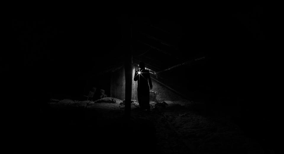 people man alone attic roof dark dirty dust old black and white light flash light
