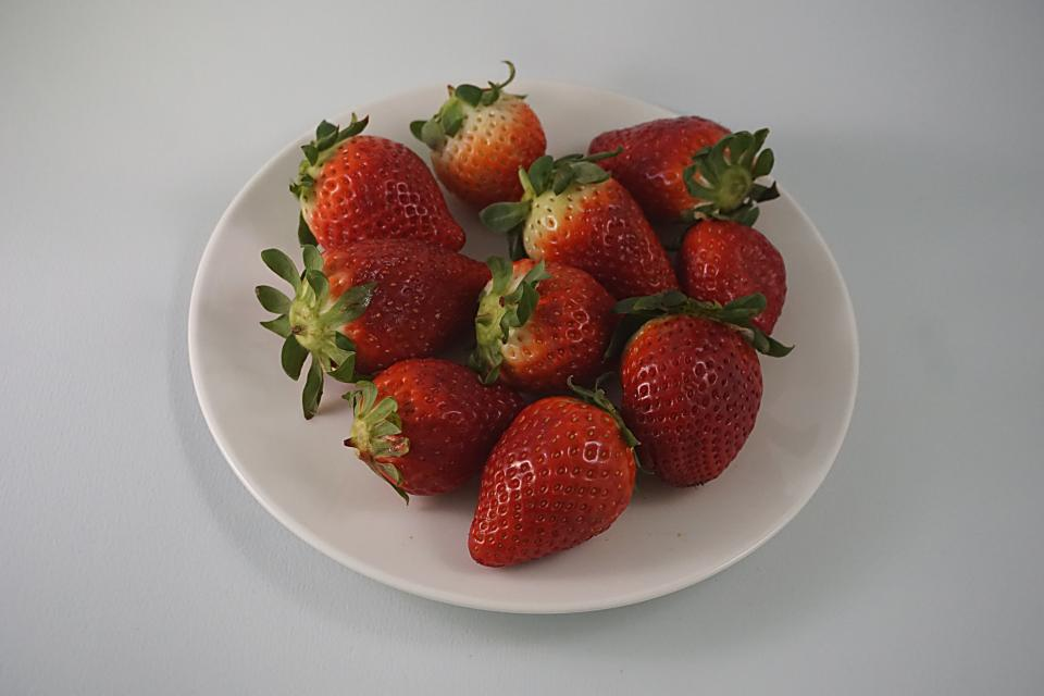 red plant seeds fresh strawberry fruit food white plate green leaves