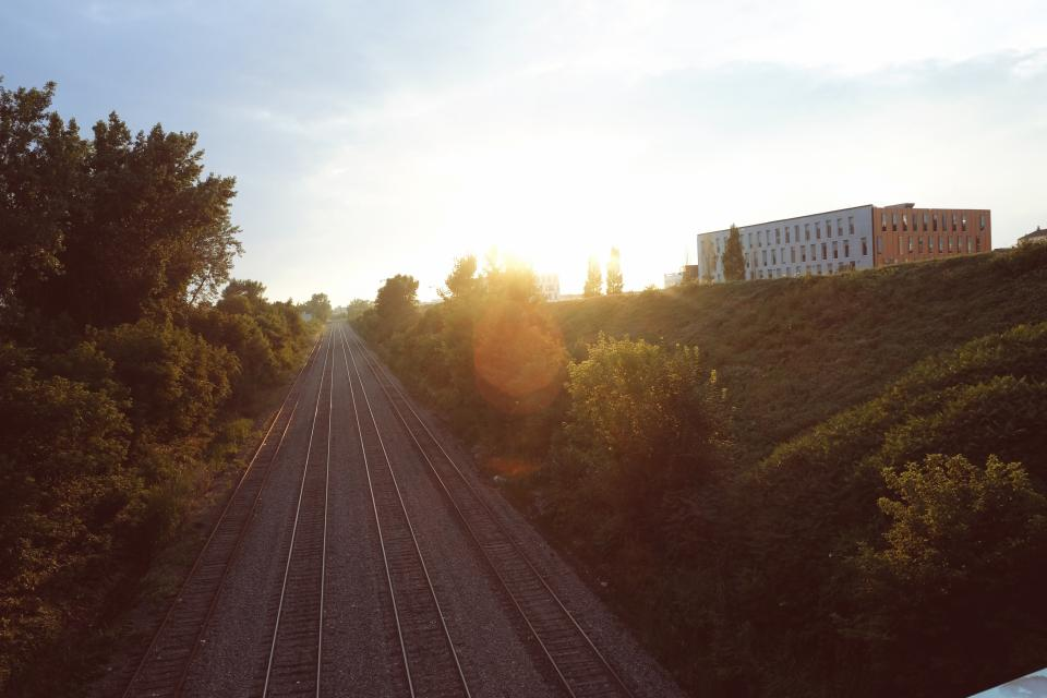railroad railway transportation train tracks sunrays sunshine trees grass stones gravel sky