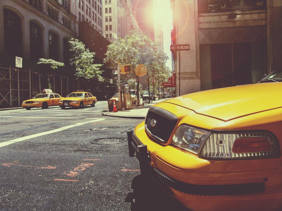 yellow taxis cabs new york city streets roads intersection buildings towers signs cars pavement manhole