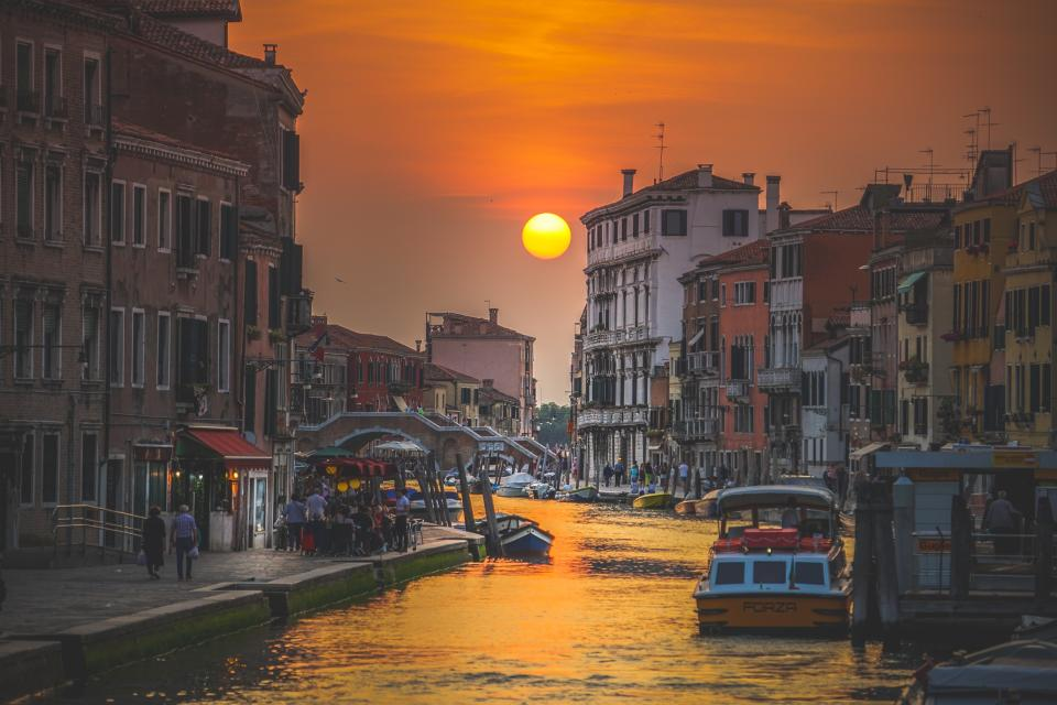 canal water boat sailing buildings italy sunset view sky people travel