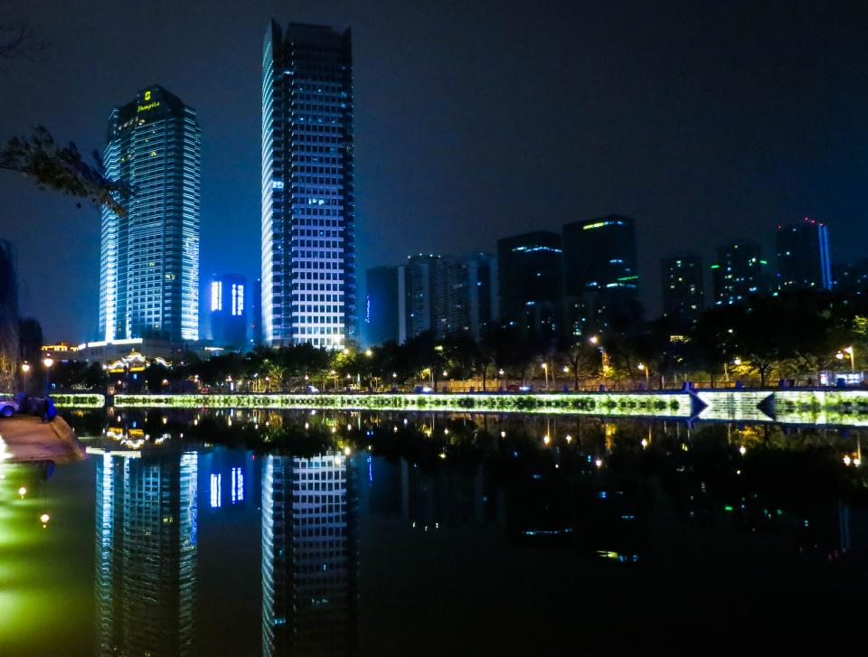 skyline buildings towers night dark city water reflection lights Chengdu China