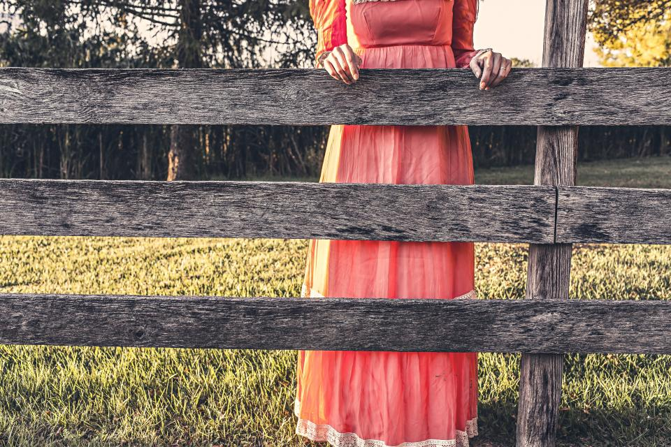 girl woman pink dress wood fence country grass field