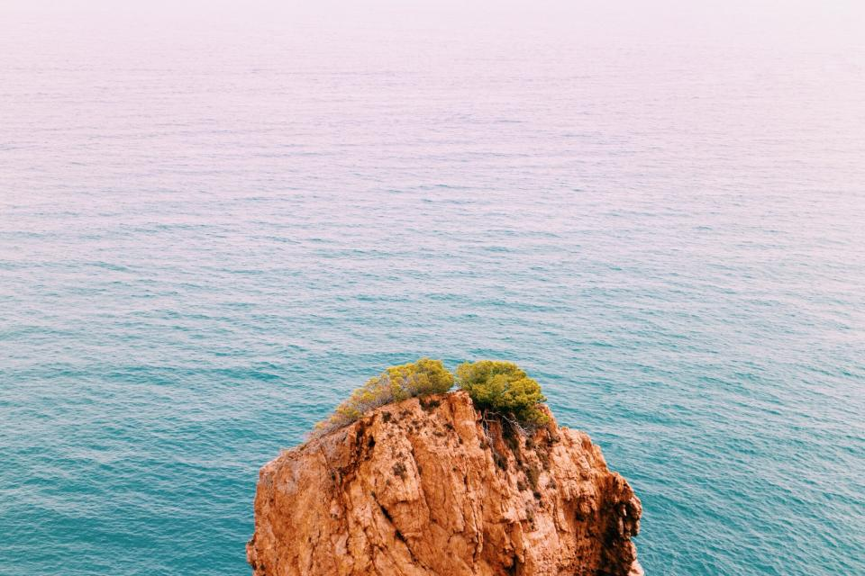 sea ocean blue water waves nature rocks hill cliff landscape view green trees plant