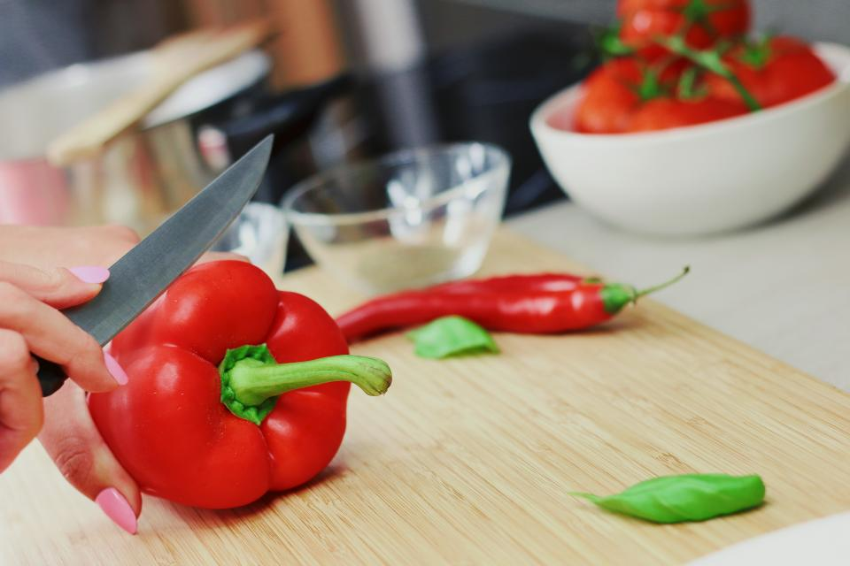 red peppers vegetables cooking cutting board knife kitchen fingers bowls ingredients