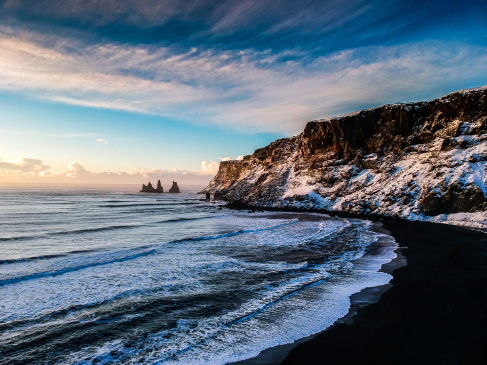 winter ocean cliffs snow cold water sand sky clouds sunlight landscape scenic travel explore wanderlust waves beach coastal shoreline iceland motion tide sea seascape