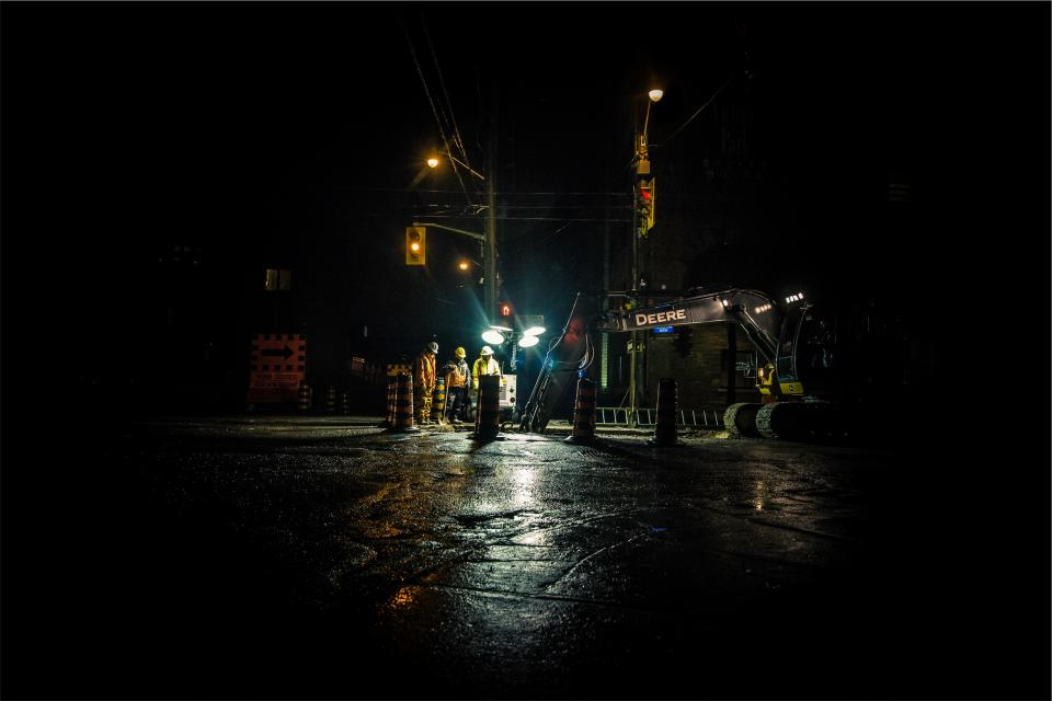 construction workers hard hats equipment backhoe streets roads deere traffic lights night dark city lamp posts