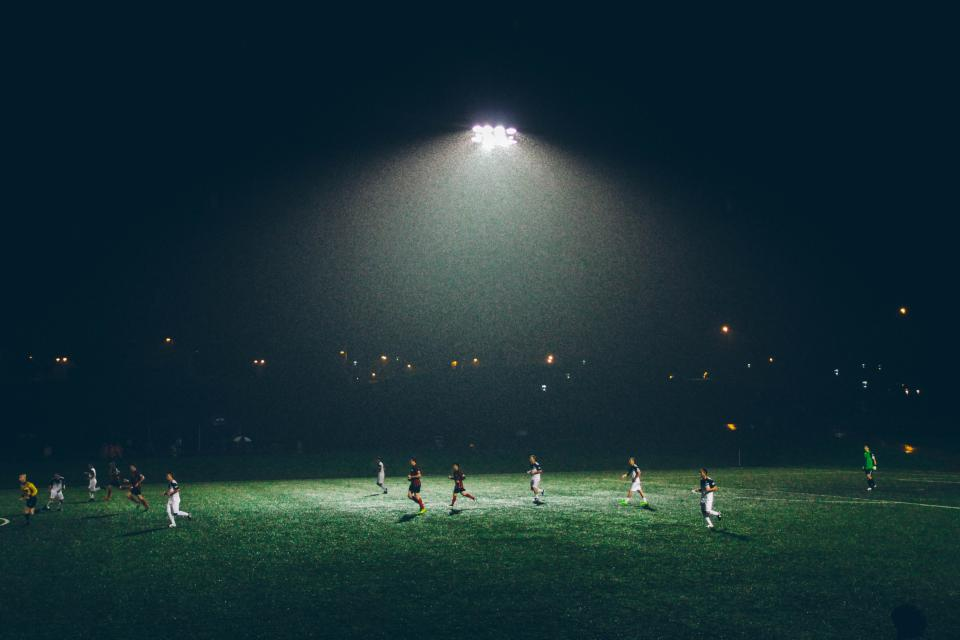 soccer field athletes sports game lights night dark fitness players team