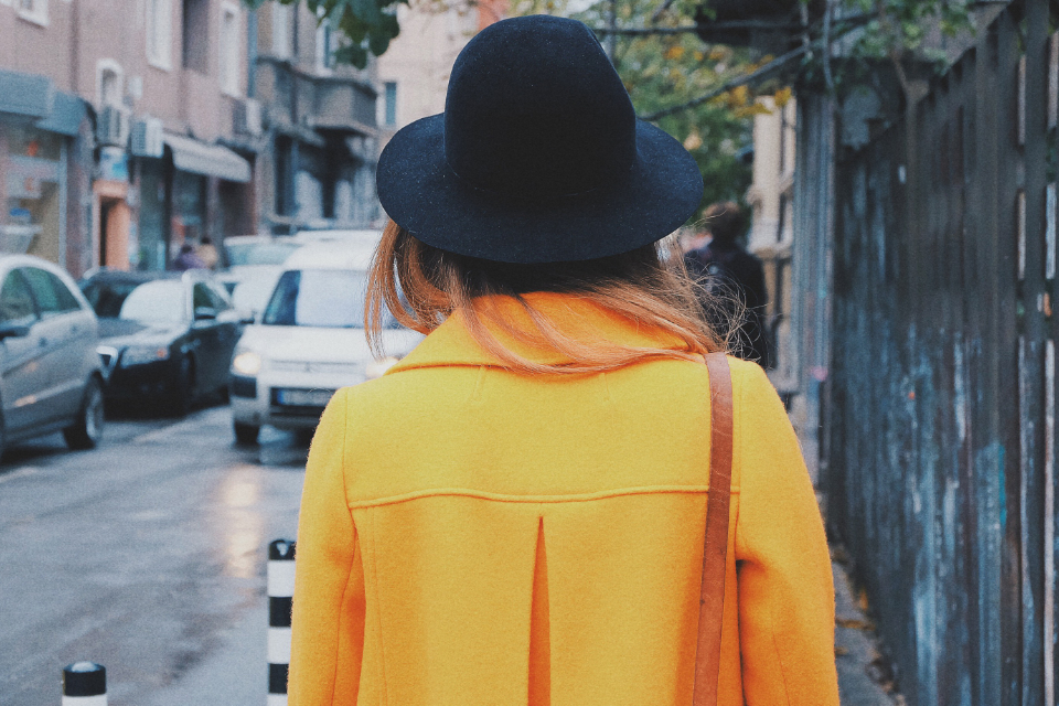 person woman young style fashion yellow coat hat back walking city urban female street outdoors