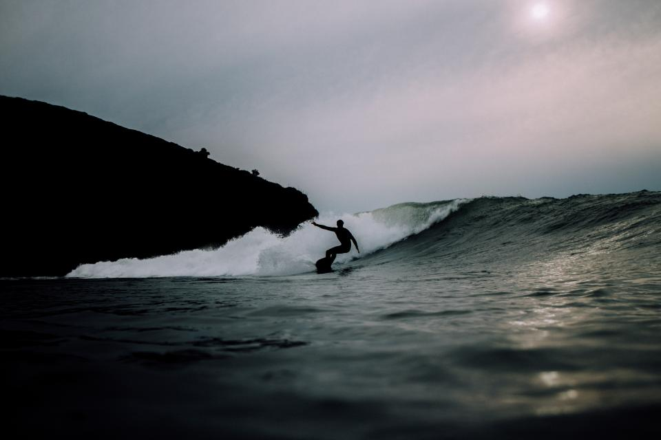 sea ocean water waves nature surfing people man dark silhouette rock cliff sky