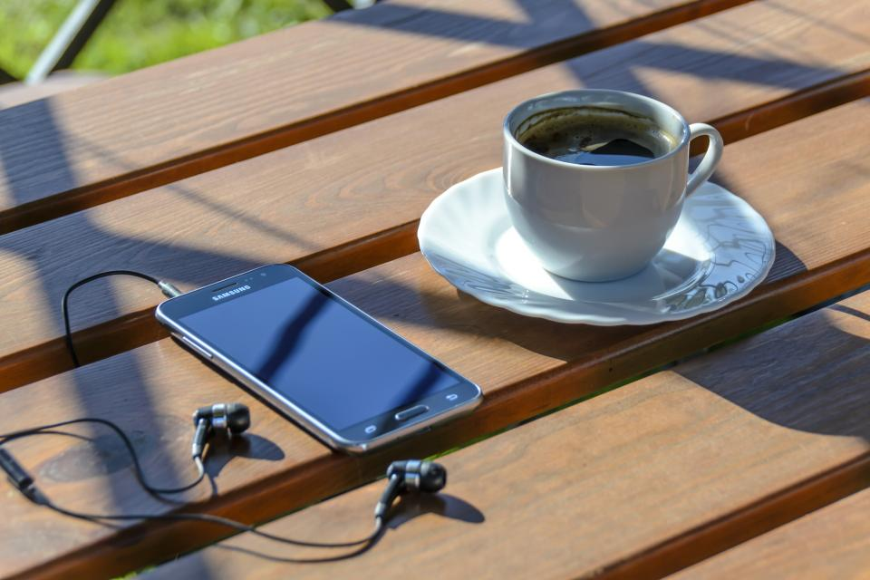 technology gadgets smartphone mobile samsung ear plugs buds cup saucer coffee tea wood bench light shadows outdoors break relax