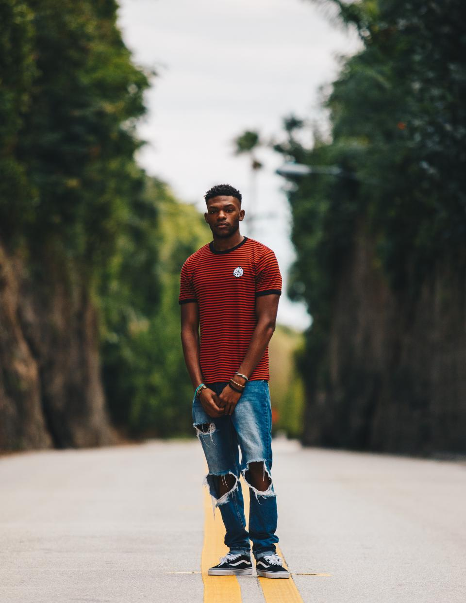 people guy man forest road bokeh ripped jeans trees trunk path bracelet red black african american curly lane