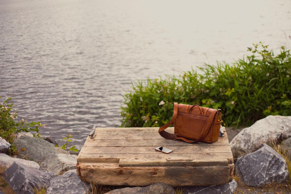 bag leather wooden outdoor mobile phone water rocks grass vacation adventure brown nature