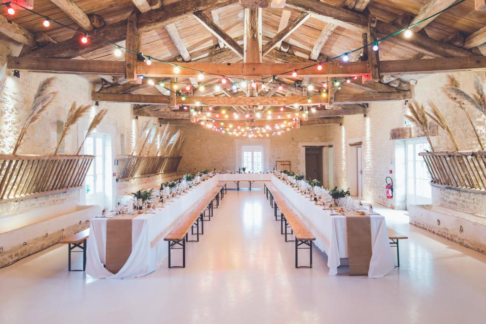 events venue banquet hall wedding party lights wood beams benches table spread eat dine white
