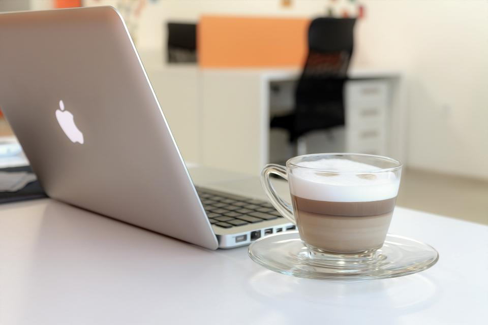laptop computer modern technology electronics internet browser macbook apple research study business work blur cup saucer cappuccino coffee office
