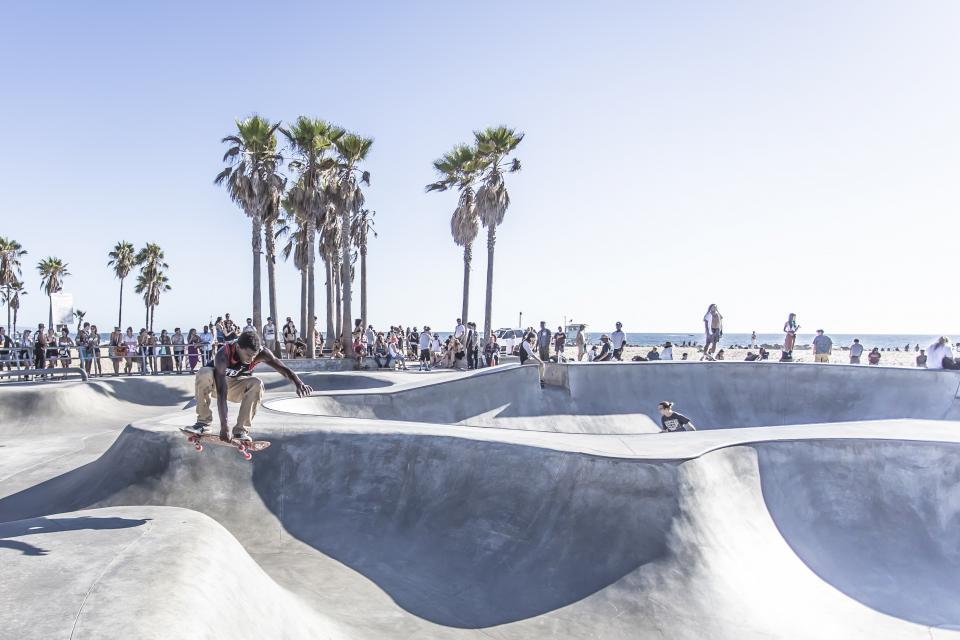 skateboard skater skate park half pipe jump people crowd spectators sports palm trees beach sand ocean sea sky sunshine summer city