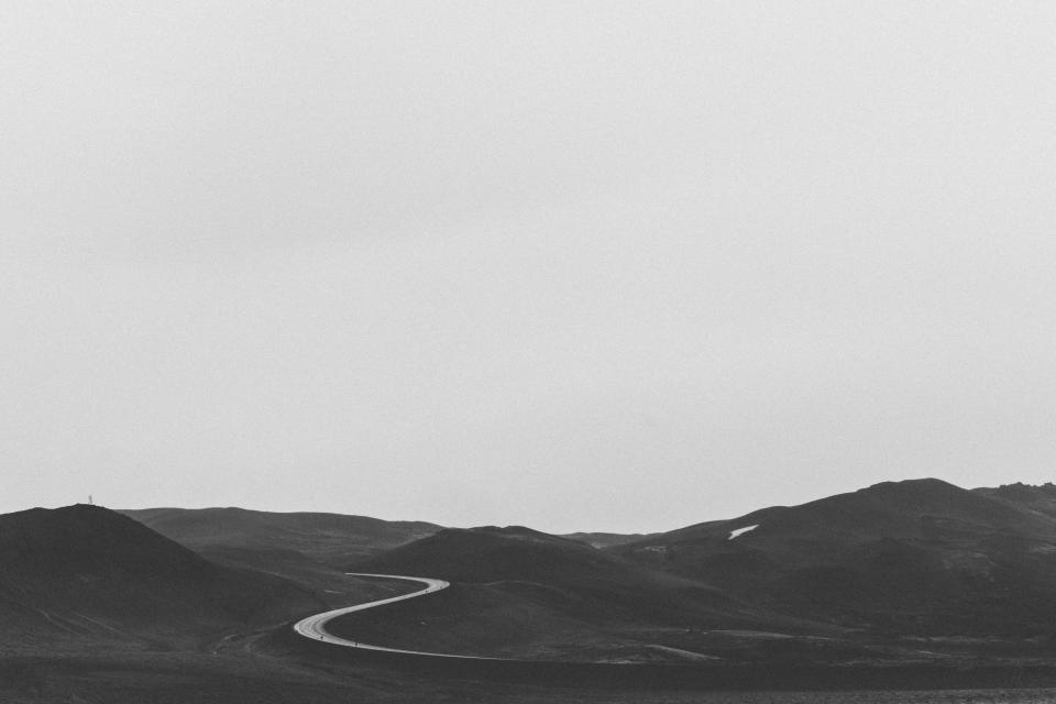 rural road countryside mountains hills field nature landscape grey sky black and white