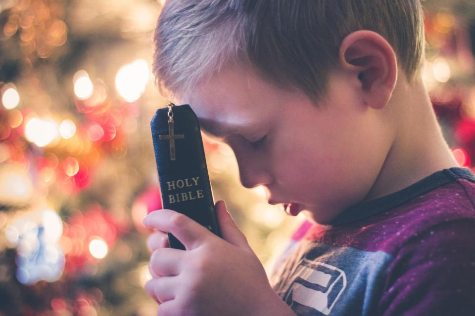 cross holy book bible reading religious hand bokeh kid praying child boy