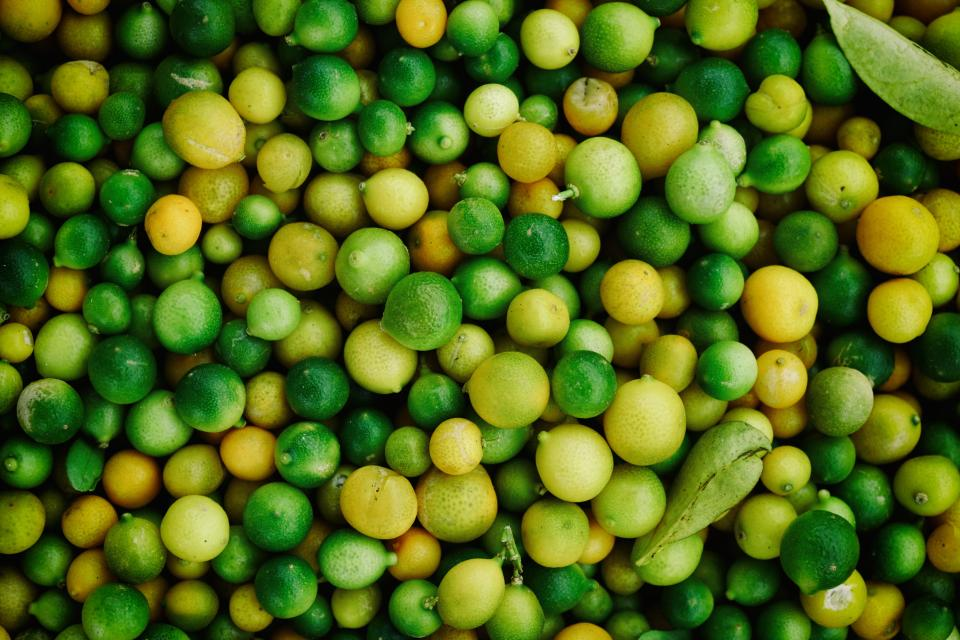 food fruits lemon lime citrus group pile spheres leaves green yellow