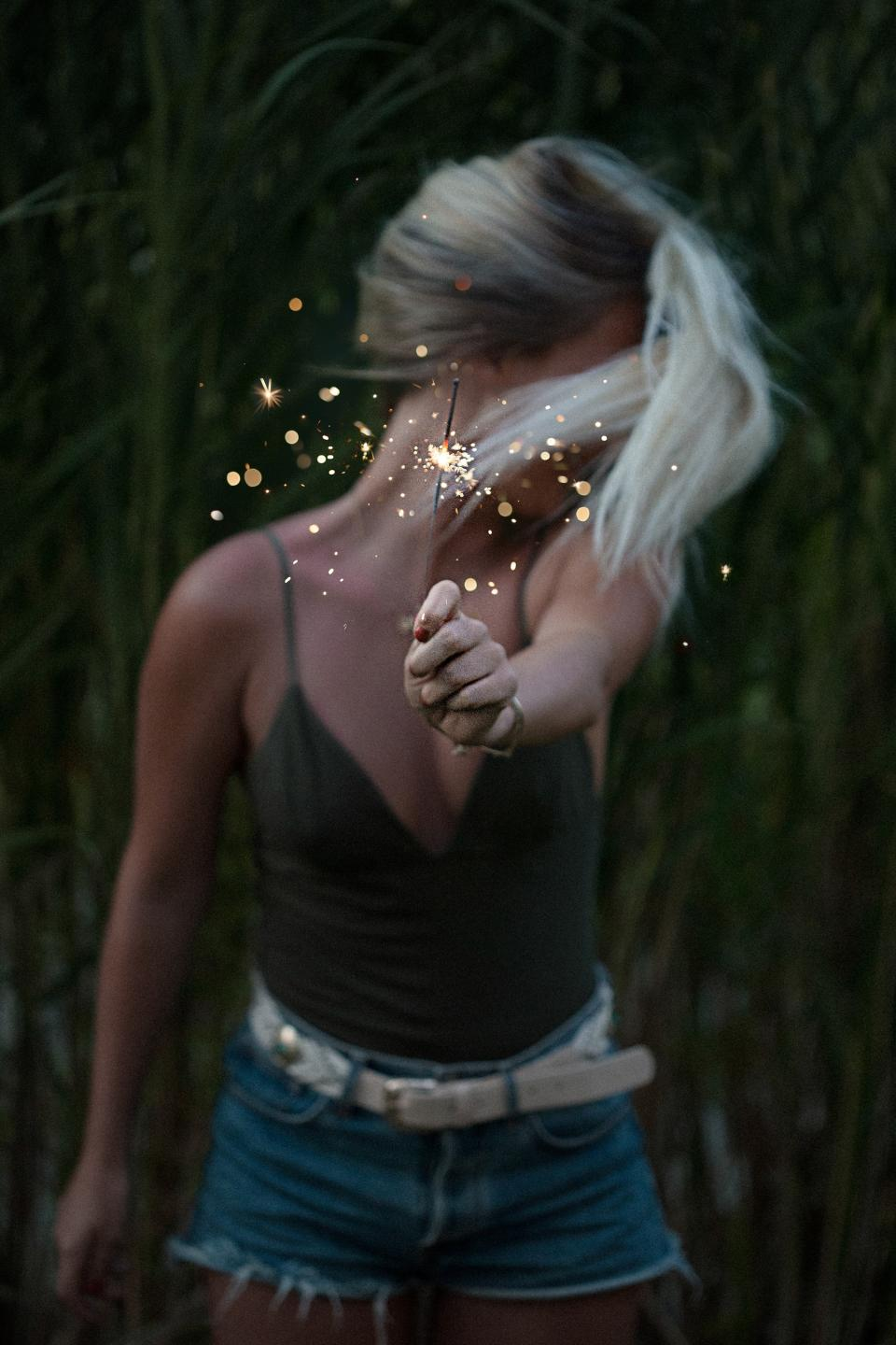 woman girl lady people stand fashion style hold out sparklers fireworks sparkle crackle sparks light orbs celebrate field leaves still bokeh beauty