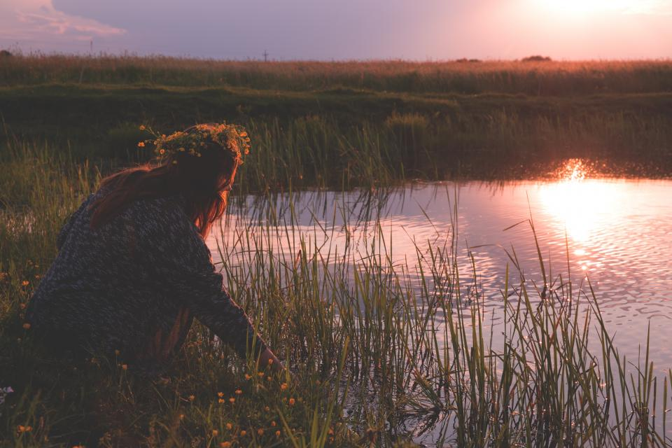 woman girl lady people bend crouch lake grass flowers play water reflection sky clouds horizon sun light dusk dawn shadows silhouette