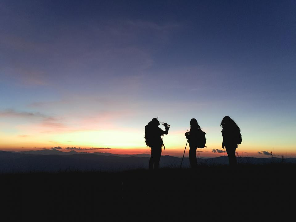 people friends woman man hiking mountain climbing mountaineers travel outdoors adventure summit peak clouds sky sunset landscape view silhouette