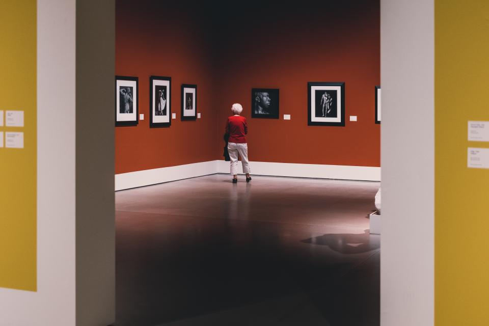 alone solo art gallery museum travel red sad dark photography photographs frames artworks old woman people
