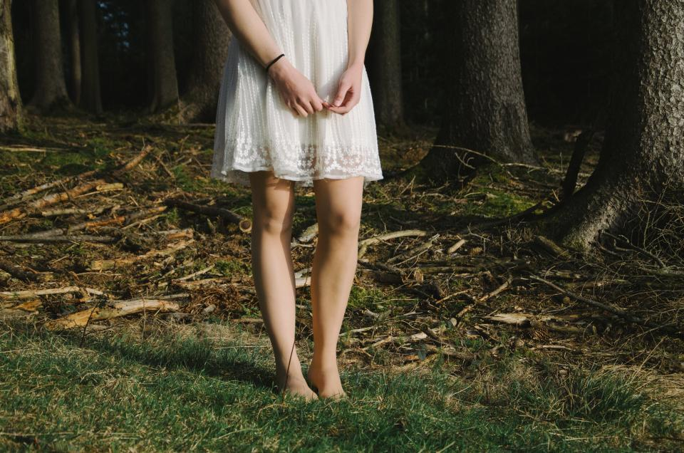 girl woman hands arms legs feet grass branches trees wristband dirt woods bark