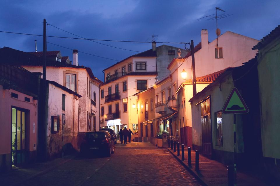 cobblestone streets sidewalk buildings shops stores houses apartments city town village people walking pedestrians night dark lights cars evening