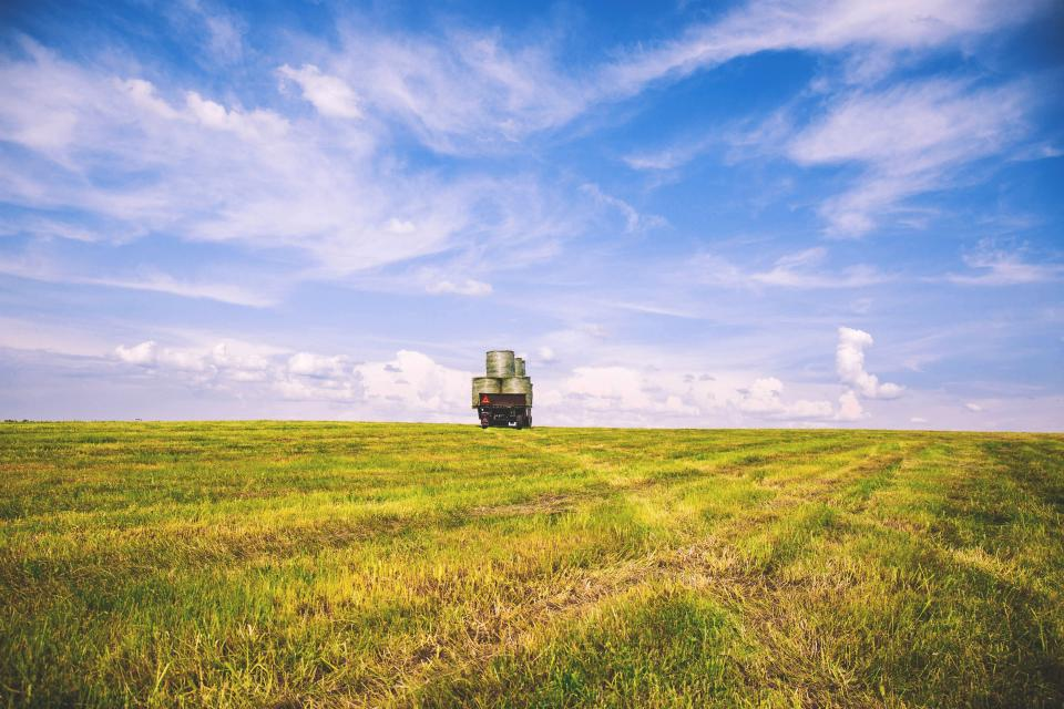 nature plains field grass harvest sky clouds horizon truck balots