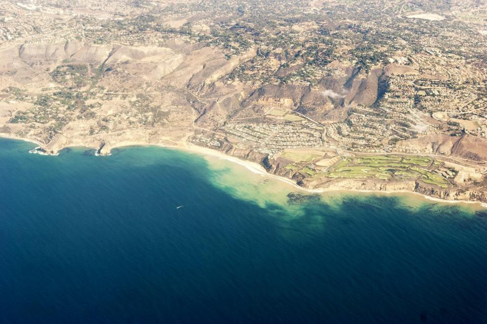 overhead view clear blue water beach boat golf course desert hot hills aerial