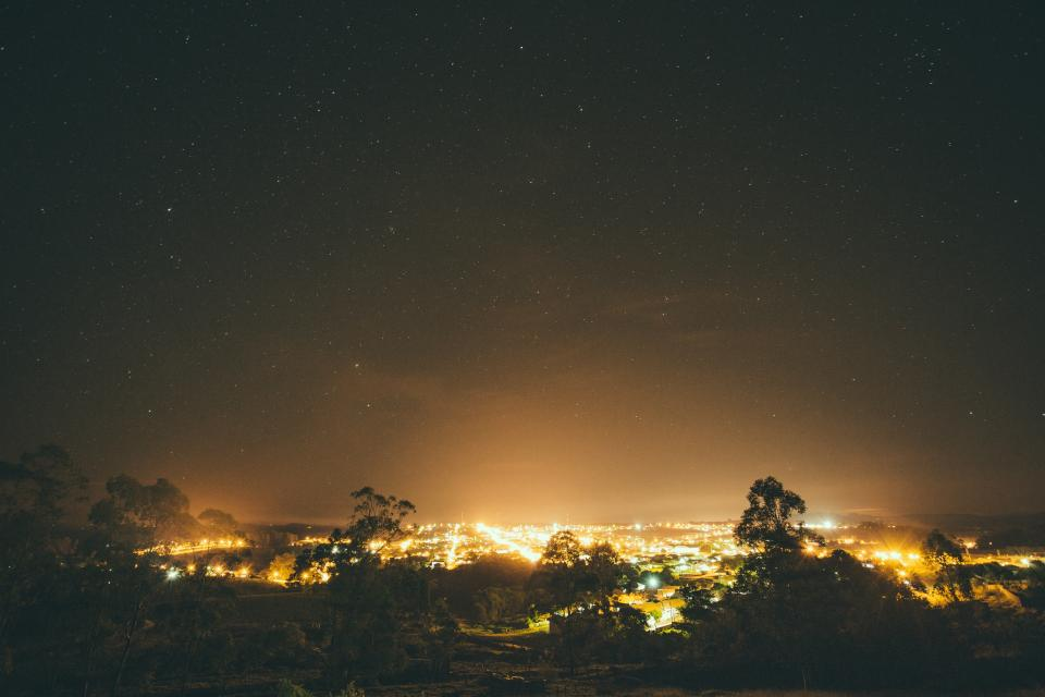 nature landscape night sky trees overlooking city lights illumination silhouette