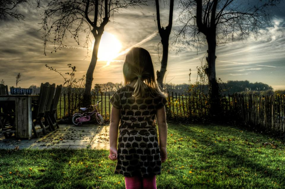 young girl child bike backyard fence grass sunset sky clouds trees hdr