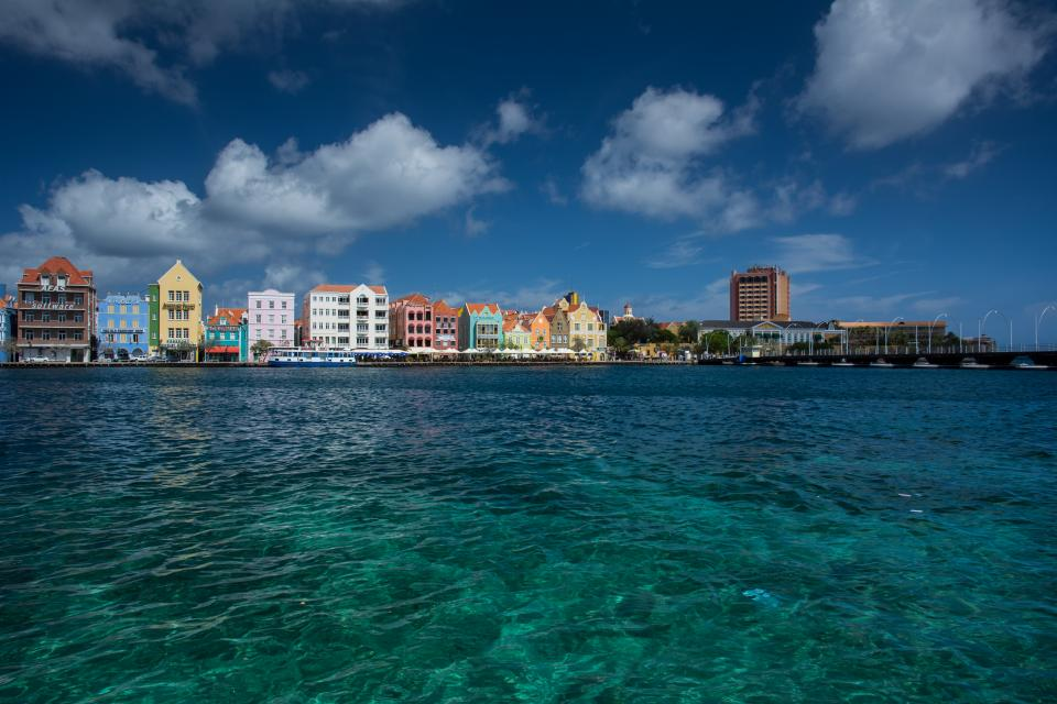 Willemstad Curaçao island caribbean buildings architecture skyline colors sky clouds boardwalk dock pier boats sea