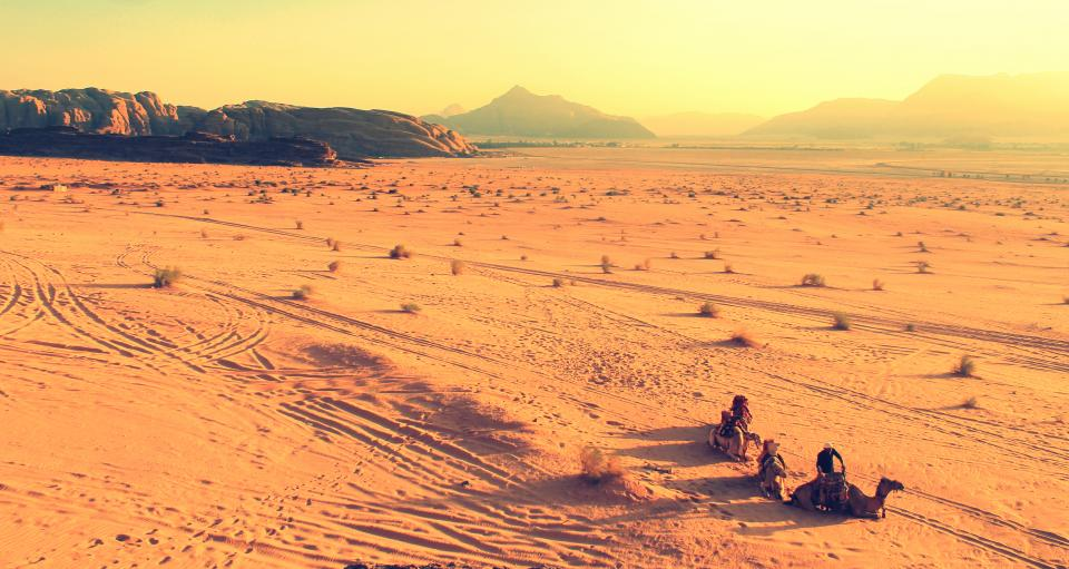 nature landscape desert sand dunes stretch bushes camels people ride travel trek traverse expanse mountains patterns gradient brown beige yellow