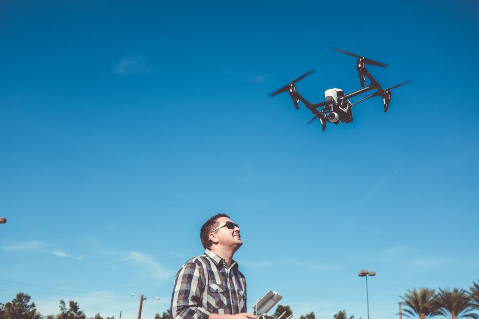 flying camera drone gadget technology aerial modern photography outdoor guy sunglasses happy smile sky blue trees