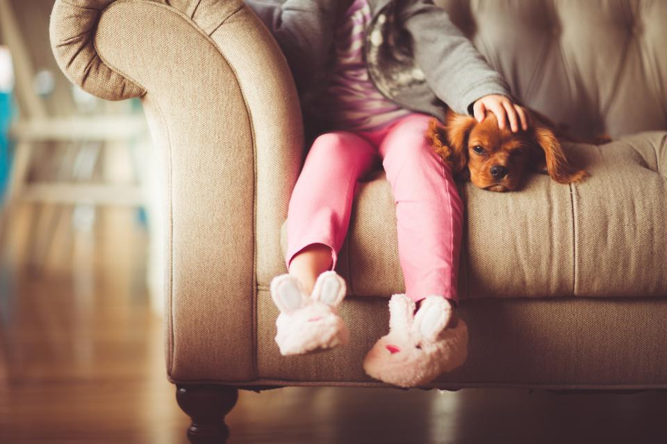 girl child person people sit comfortable fluffy adorable bunny slippers fashion style pink dog pet couch house residence living room friends family