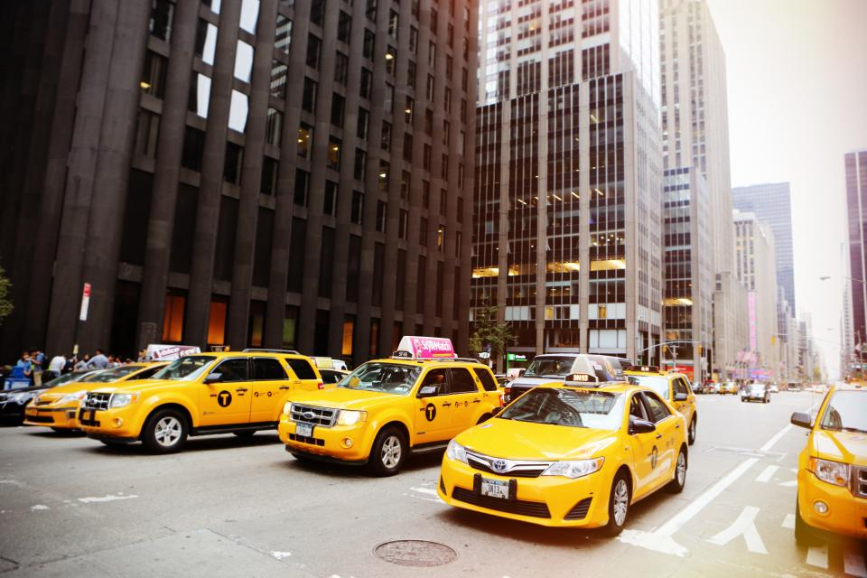 taxis cabs yellow new york city street road buildings towers manhole windows